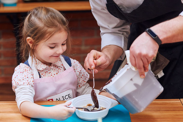 Girl looking at chocolate being poured by man in bowl