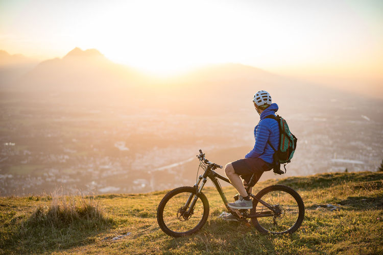 Side view of man riding bicycle on mountain against landscape during sunset