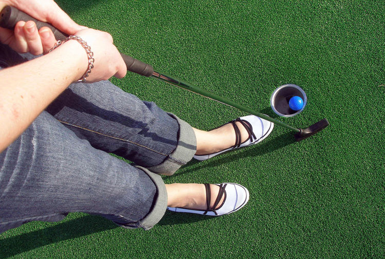 Putting a ball at an adventure golf. Golf Activity Adult Ball Body Part Crazy Golf Day Golf Ball Grass Green Color High Angle View Human Body Part Human Foot Human Leg Human Limb Leisure Activity Lifestyles Low Section Mini Golf Nature One Person Outdoors Plant Sport Women