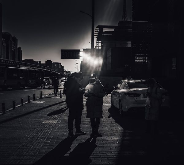 Rear view of people walking on road at night