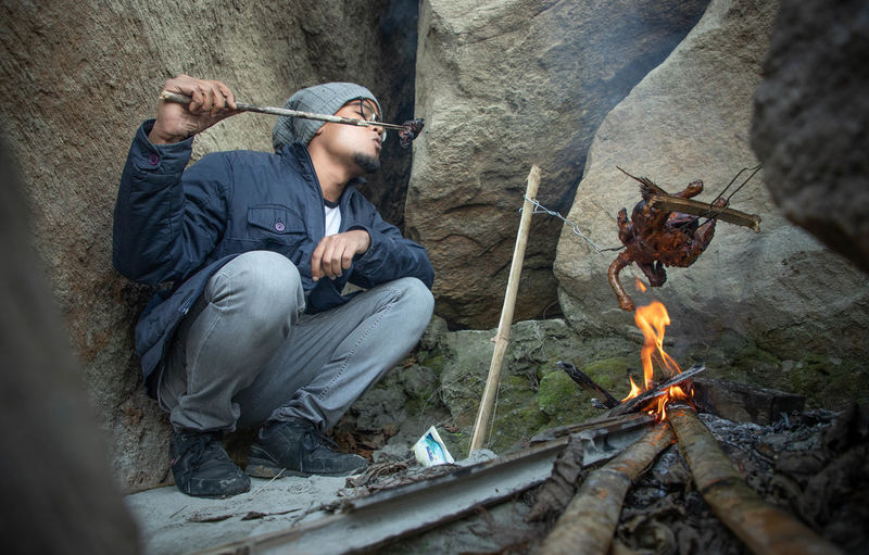 Man roasting meat over fire while sitting by rocks