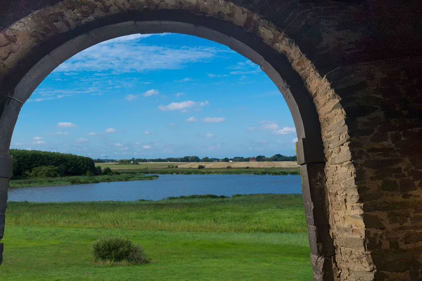 Panoramic view of the swimming, fishing and nature area Eixen lake. Shot looking through a door arch. Sky Grass Plant Cloud - Sky Nature No People Day Architecture Arch Land Scenics - Nature Field Water Environment Green Color Landscape Tree Beauty In Nature Tranquil Scene Outdoors