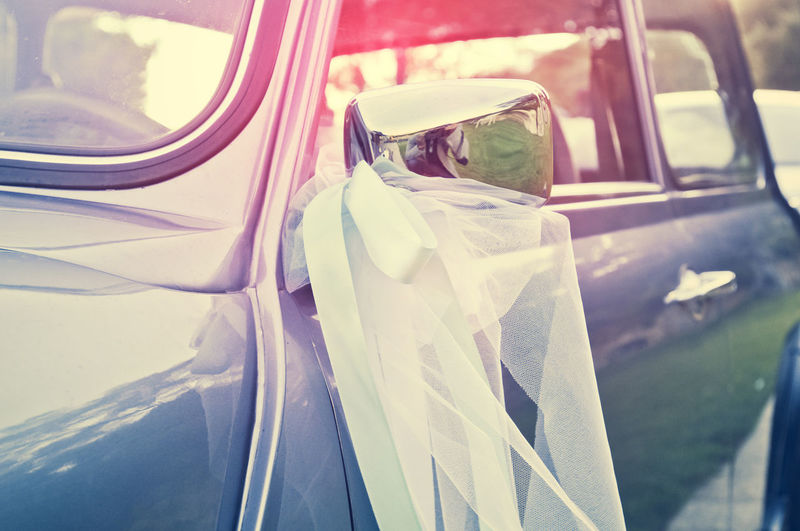 Ribbon Bow Hanging From Side-View Mirror Of Car During Wedding Ceremony