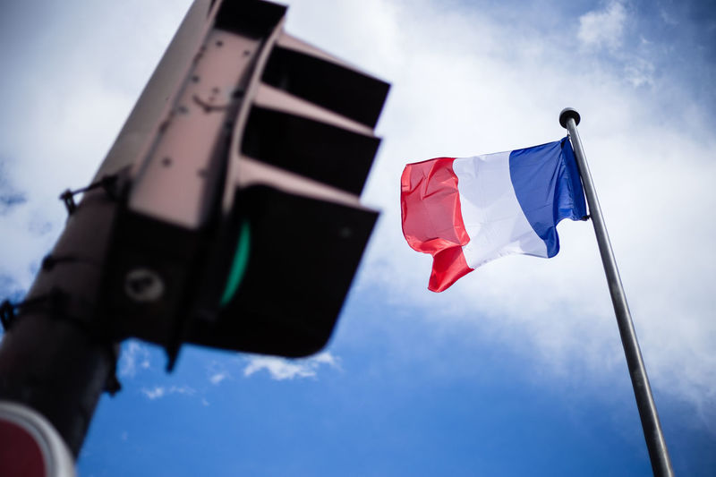 Low angle view of flags and road signal against sky