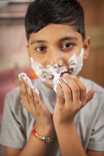 Close-up portrait of boy holding camera