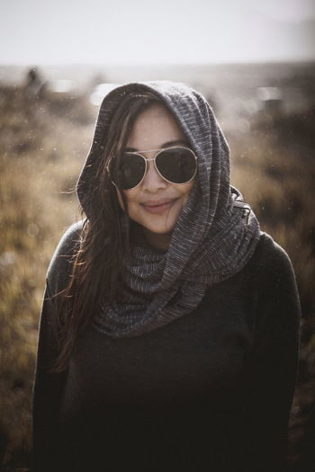 Smiling young woman wearing sunglasses against sky