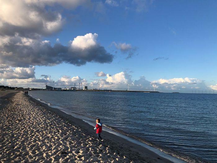 High angle view of boy walking at shore of beach