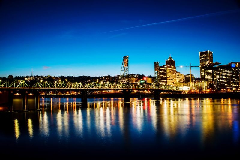 Illuminated City By River Against Blue Sky