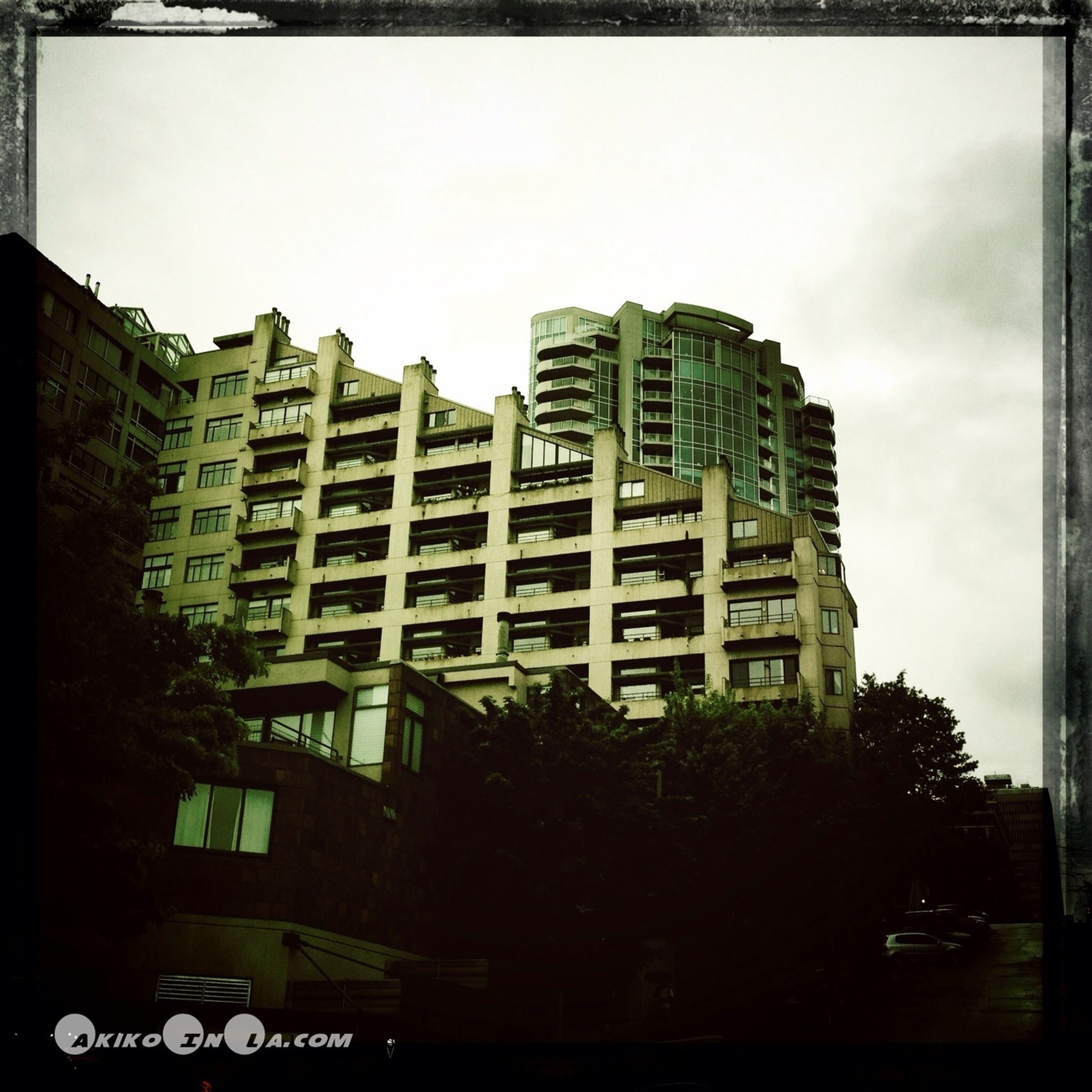 building exterior, architecture, built structure, transfer print, city, low angle view, building, sky, auto post production filter, window, residential building, clear sky, residential structure, tree, apartment, day, city life, outdoors, no people, tall - high