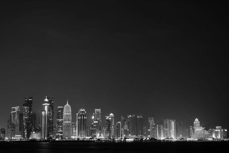 Illuminated skyscrapers against sky at night