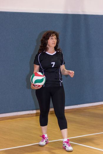 Front view of mid adult athlete holding volleyball ball