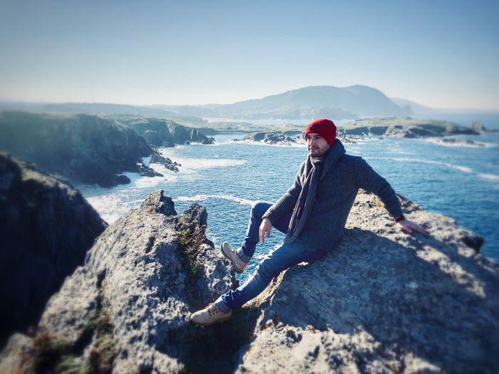 Man looking away while sitting on rock against sky