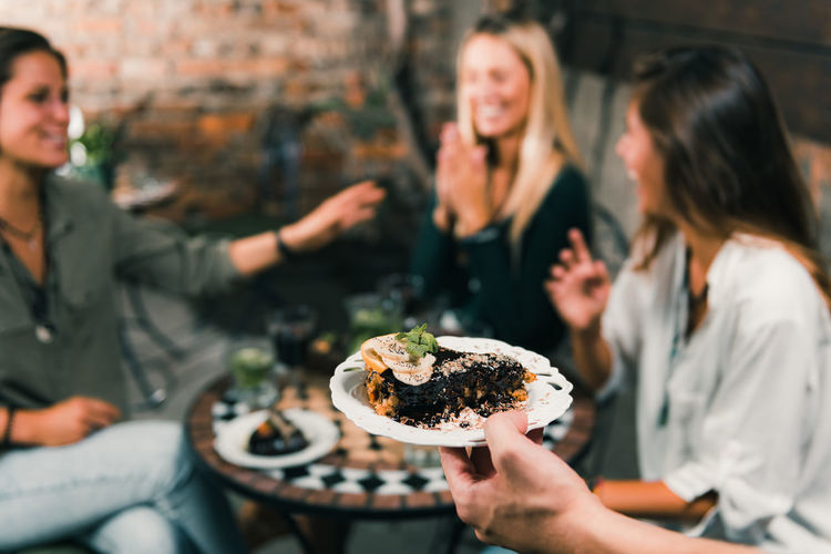 Waiter Bringing A Plate With Raw Cake To Female Friends. Waiter Hand Cake Raw Plate Serving Lifestyle Restaurant Vegetarian Sweet No Sugar Women Food Friends Meal Wine Red Wine Red Alcohol People Diet Healthy Eating Vegan Table