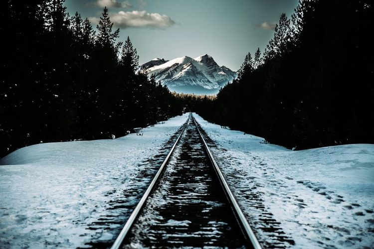 Snow covered railroad track by mountain against sky