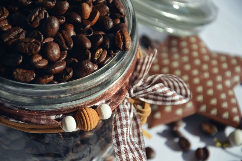Close-up of roasted coffee beans in decorated jar on table