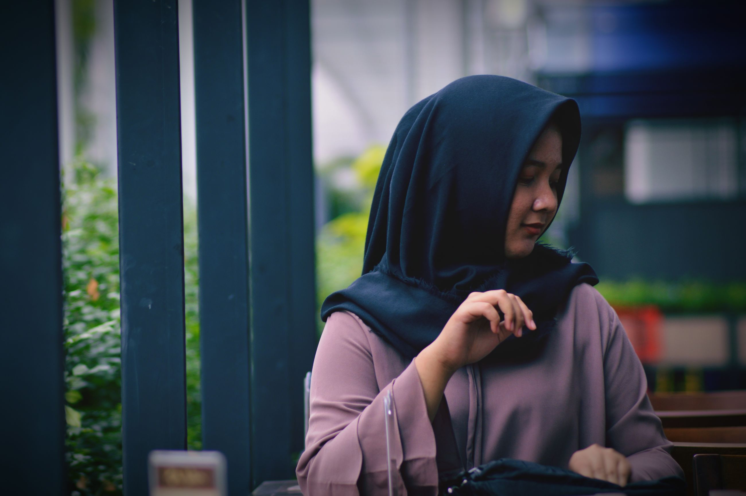 focus on foreground, hood - clothing, real people, hooded shirt, sitting, traditional clothing, one person, day, young adult, lifestyles, outdoors, young women, close-up, people