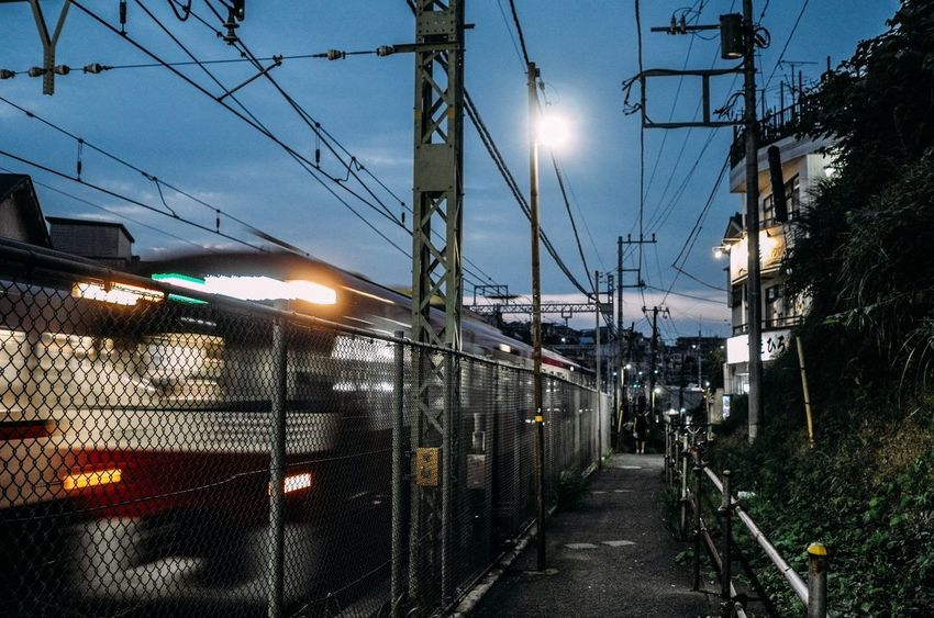 Going Home Commuter Train Train Passing Train Lights Evening Light Evening Illuminated Rail Transportation Electricity  Yokohama Walking Around The City  Walk Path Mode Of Transport Railroad Track Electricity Pylon Cable Public Transportation Light And Shadow City Life City Street Yokohama, Japan Evening Walk August August 2017