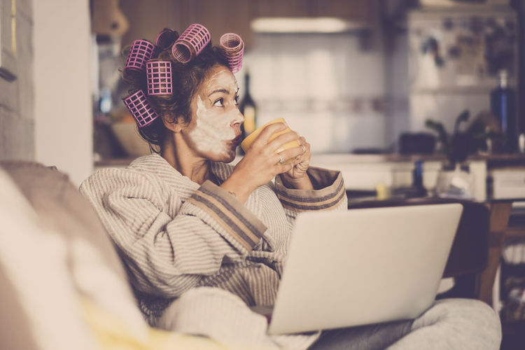 Mature woman with beauty products drinking coffee while using laptop at home