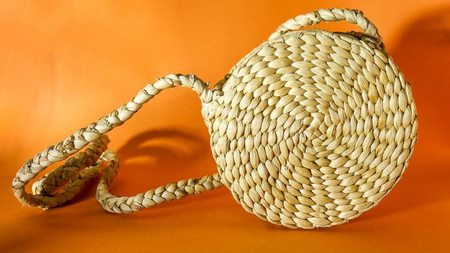 Close-up of rope on table against orange background