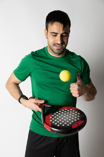 Man holding ball while standing against white background