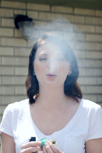 Portrait of young woman smoking bong against wall