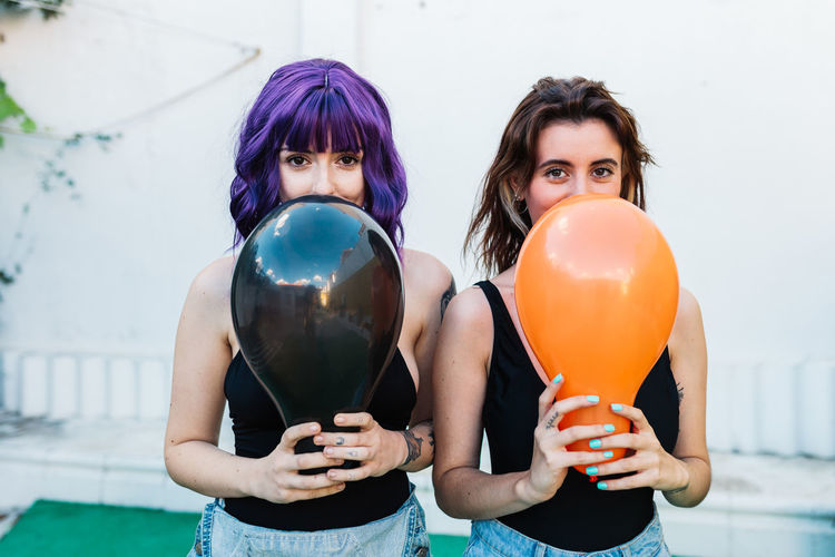 Portrait of women holding balloons while standing on land
