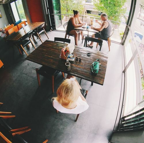 Adult Casual Clothing Child Childhood Food And Drink Group Of People Hairstyle High Angle View Indoors  Leisure Activity Lifestyles Men People Real People Rear View Restaurant Seat Sitting Table Women