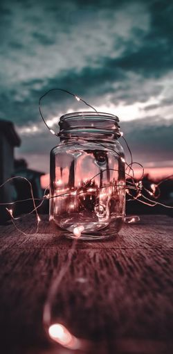 Close-up of glass jar on table against sky during sunset