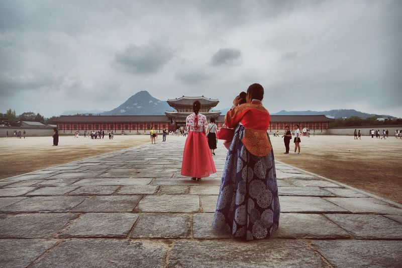 Gyeongbokgung Palace (경복궁) Cloud - Sky Cloudy Costume Day Girls Leisure Activity Lifestyles Medium Group Of People Mountain Mountain View Nature Outdoors Posing Red Sky Temple The Way Forward Tourism Tourist Traditional Clothing Travel Destinations Vacations Walkway