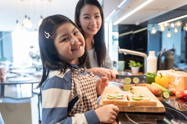 Daughter and mother preparing the sandwich and salad for breakfast in kitchen. Mom Mother Daughter Girl Girls Asian  Home Family Love Preparation  Preparing Food Sandwich Kitchen Women Child Smiling Females Childhood Togetherness Parent Happiness Food And Drink Family With One Child Food Bonding Portrait