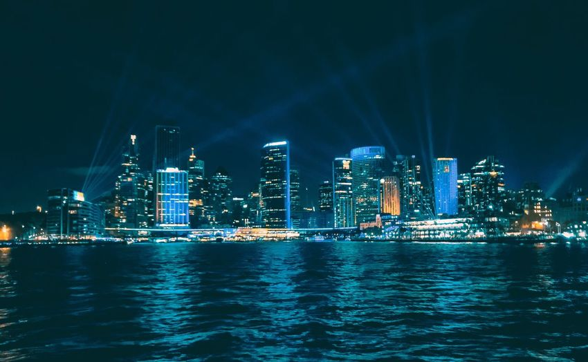 Illuminated buildings by sea in city at night