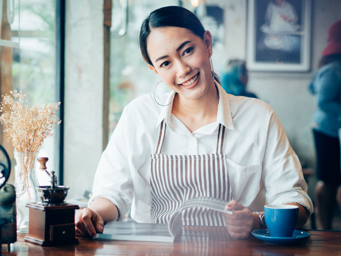 Portrait of smiling woman with magazine in cafe