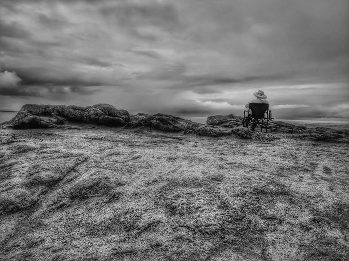 Rear view of man sitting on seat at beach against sky