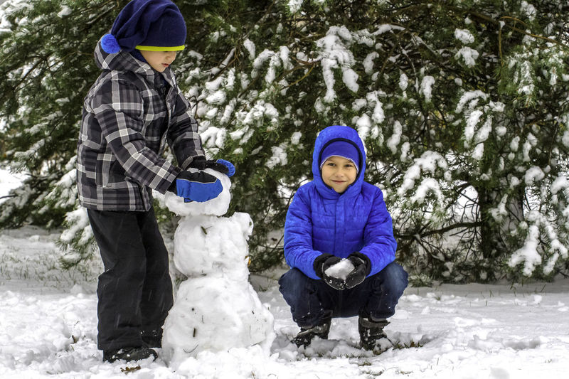 Portrait Of Boy With Brother Making Snowman During Winter