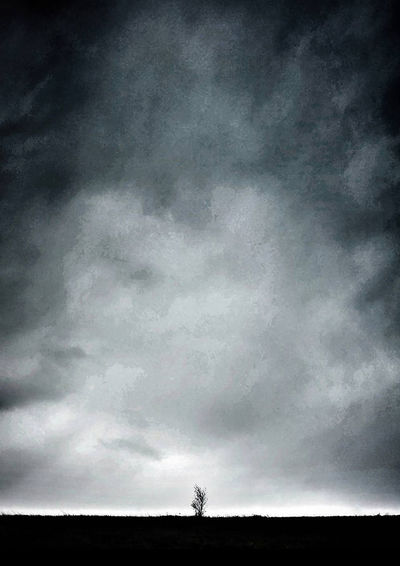 Silhouette of man on field against cloudy sky