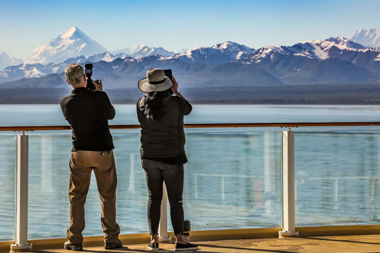 Rear View Of Man And Woman Photographing Snowcapped Mountain
