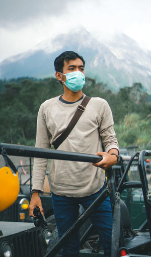 Portrait of young man with mask in car in front of mountain