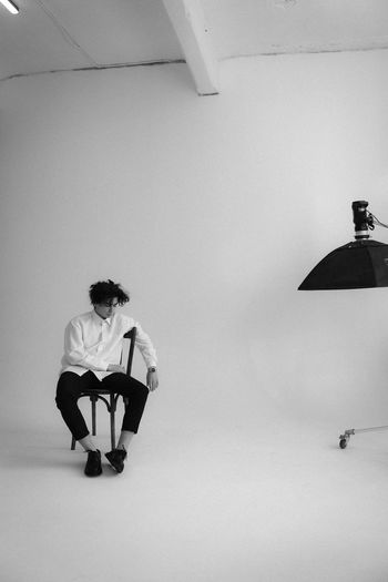 Man with umbrella sitting against wall