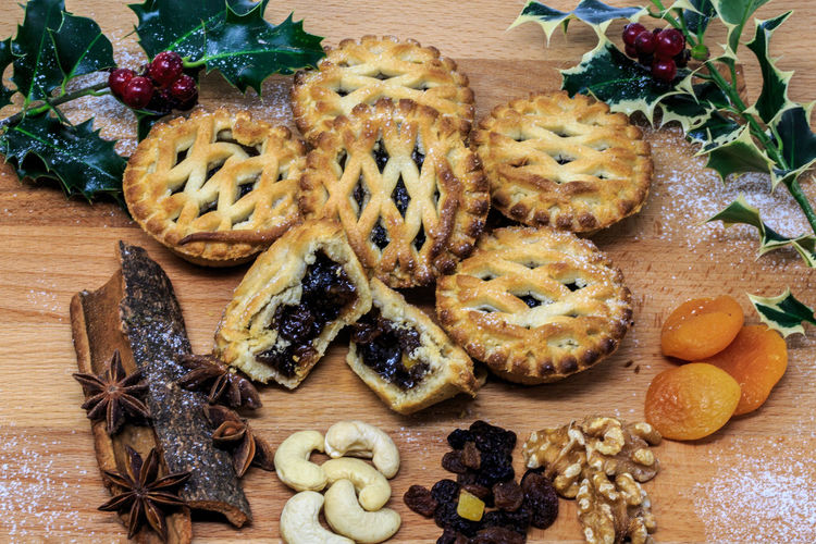 "A mince pie is a sweet pie of British origin, filled with a mixture of dried fruits and spices called ""mincemeat"", that is traditionally served during the Christmas season in the English-speaking world. Food Food And Drink Freshness Sweet Food Baked Sweet Fruit Indoors  Cookie Still Life Indulgence Christmas Close-up High Angle View Table Temptation Mince Pie Spices Desert Christmas Raisins Nuts Traditional Holly Mincemeat"