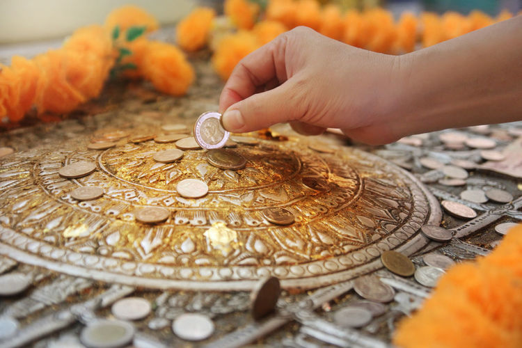 Close-up of hand putting coin into religious coin bank