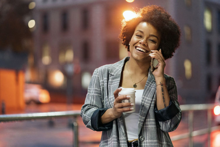 Young woman holding coffee cup talking on phone against building
