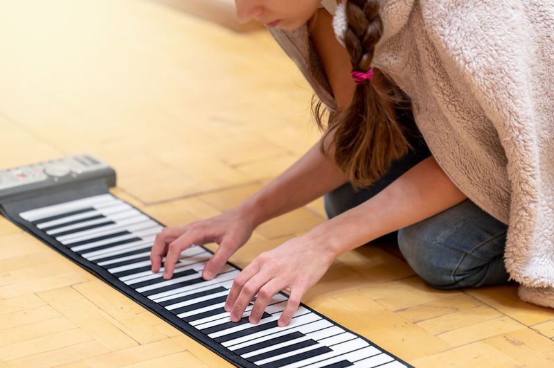 Midsection of woman playing piano at home