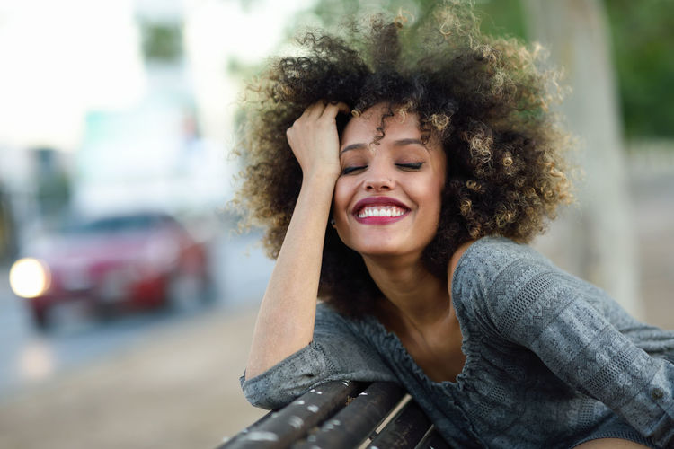 Smiling Young Woman With Curly Hair In City
