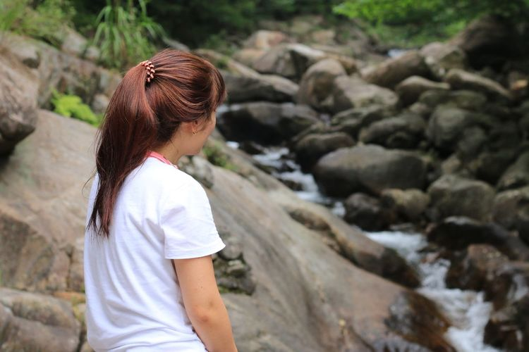 Rear view of woman looking at stream in forest