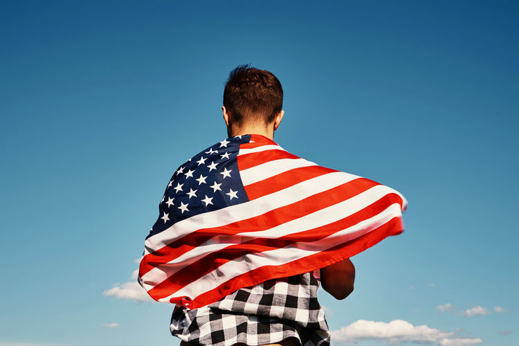 American flag outdoors. man holds usa national flag against blue cloudy sky. independence day