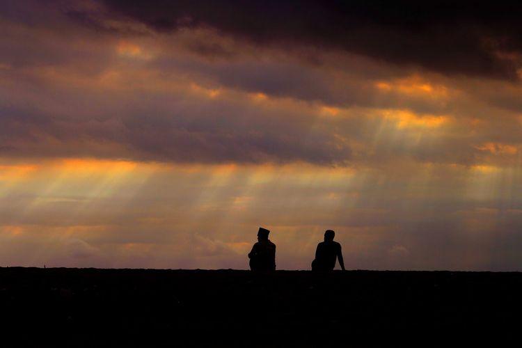 Silhouette men standing on land against sky during sunset