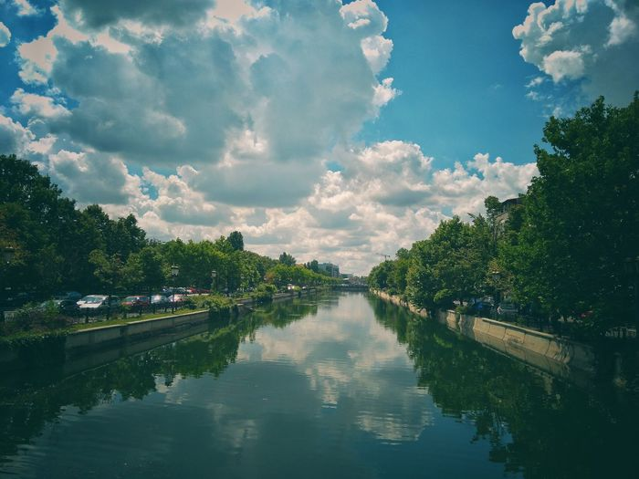 Dambovita River in Bucharest, Romania. Bucharest Dâmbovița River View Cloudscape Clouds And Sky Tree Water Reflection Sky Cloud - Sky Standing Water Lakeshore Calm Lakeside Symmetry Lake Waterfront Idyllic