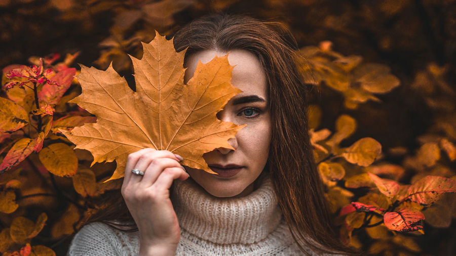 Close-up of beautiful woman holding maple leaf against face during autumn