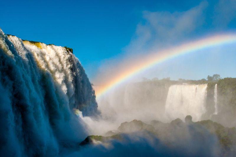 Scenic view of rainbow above iguazu falls