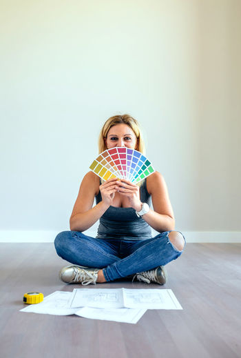 Woman with blueprint and color swatch sitting on hardwood floor at home